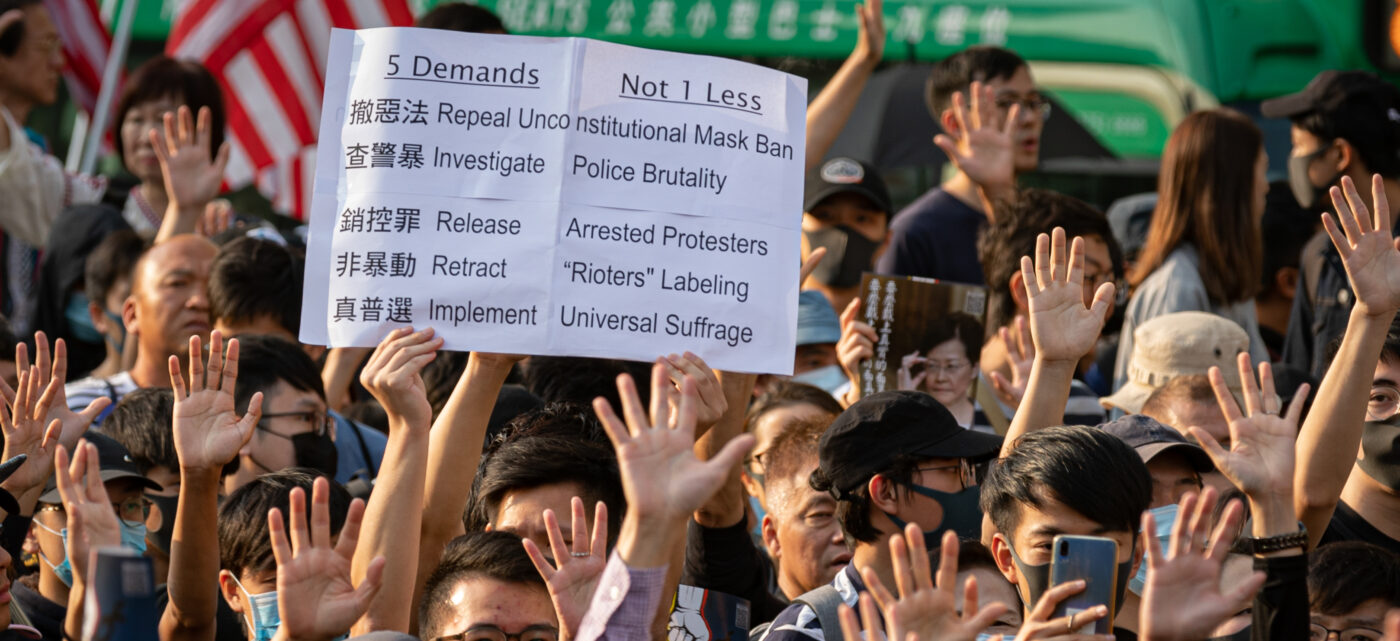 Hong Kong protester holds up a sign with their five demands in English and Cantonese.