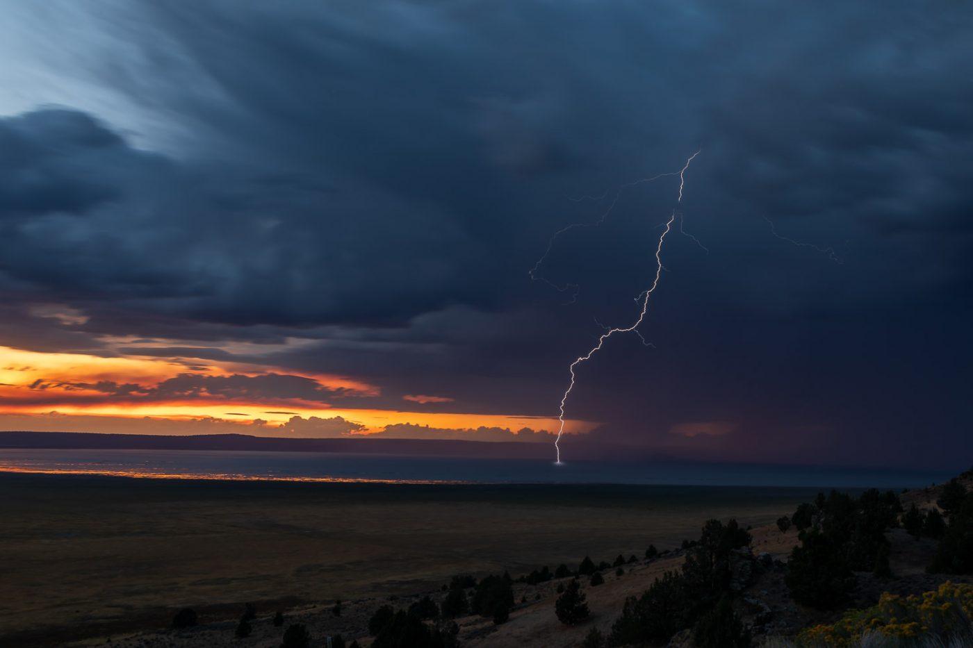 Lighting strikes Goose Lake, California with dark clouds and an orange sunset.