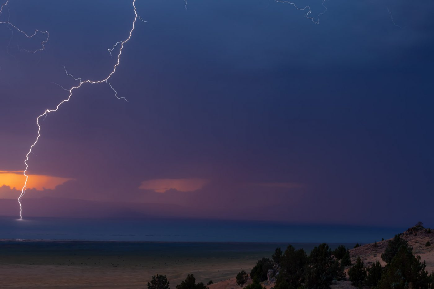 A lightning bolt strikes the surface of Goose Lake below colorful sunset clouds.