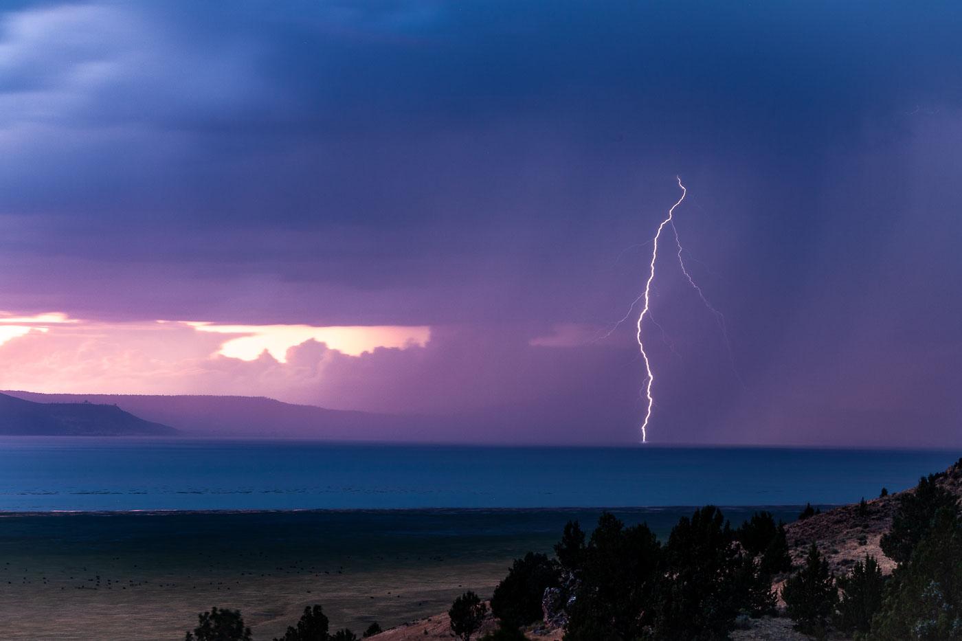 A lightning bolt strikes Goose Lake, California at sunset.