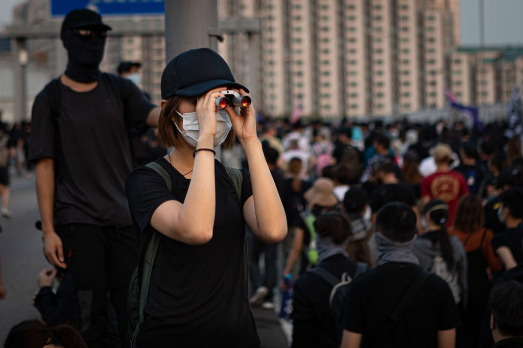 A black-clad protester in Hong Kong looks through binoculars to monitor police activity near a protest march.