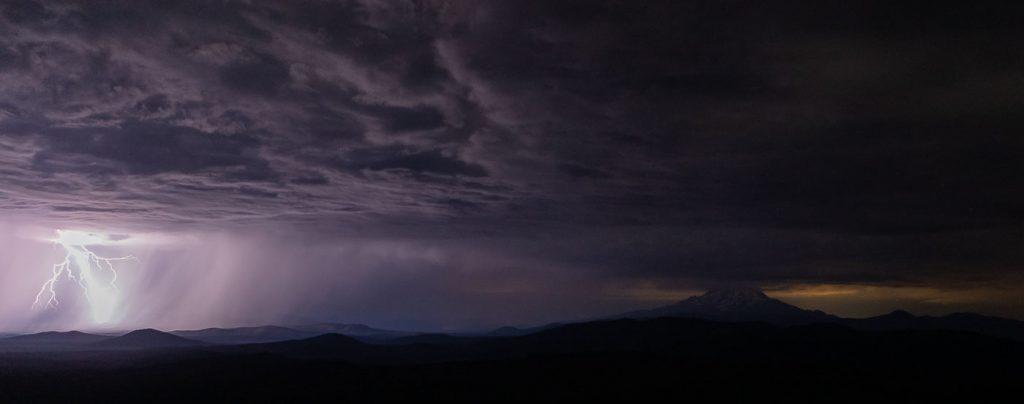 A bolt of lightning at night illuminates Mt. Shasta.