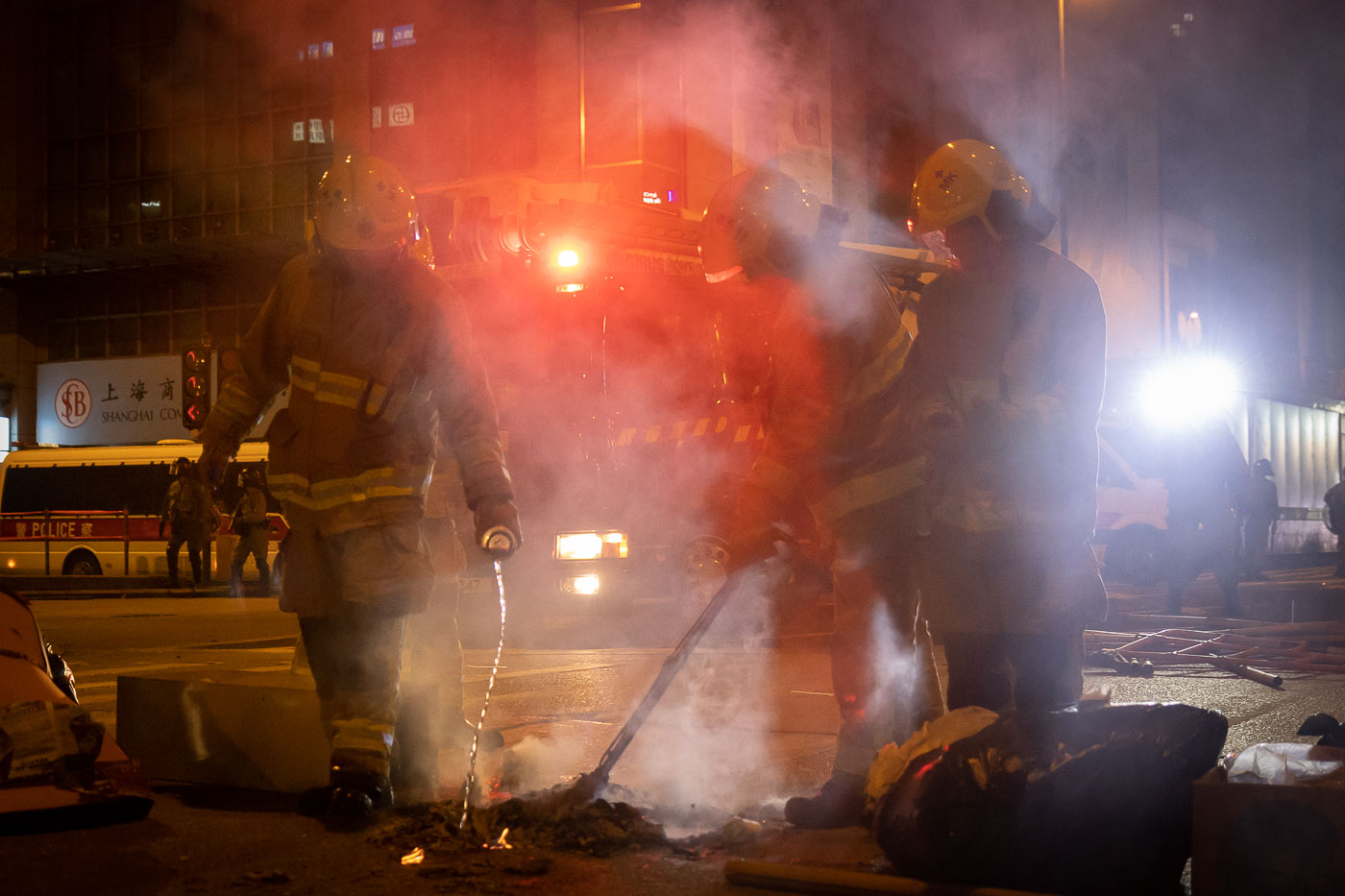 Firefighters douse a small fire in the street set by protesters in Hong Kong.