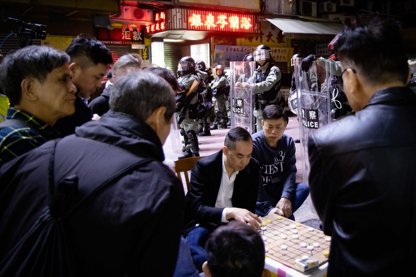 Men play Chinese Chess while Hong Kong riot police stand in background.