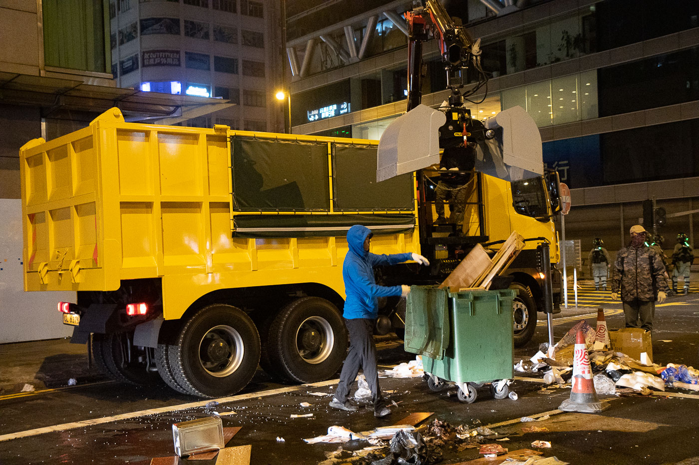 Dump truck with crane picks up barricade debris left by protesters.