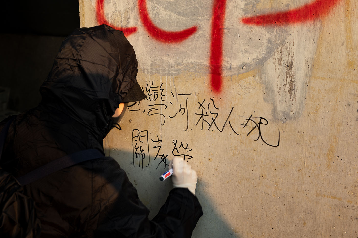 Black-clad protester writes a slogan in felt pen on a wall during Hong Kong protest march.