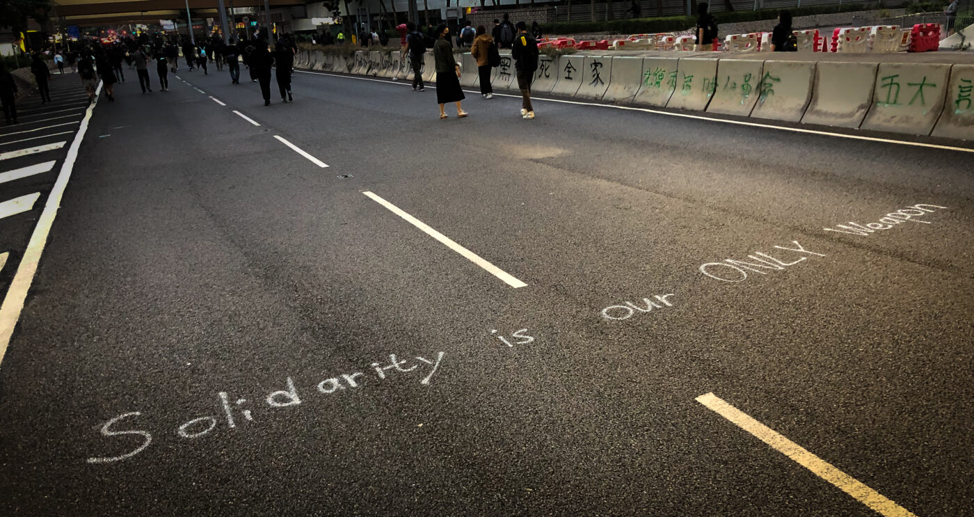 """Graffiti on street says """"Solidarity is our only weapon."""""""