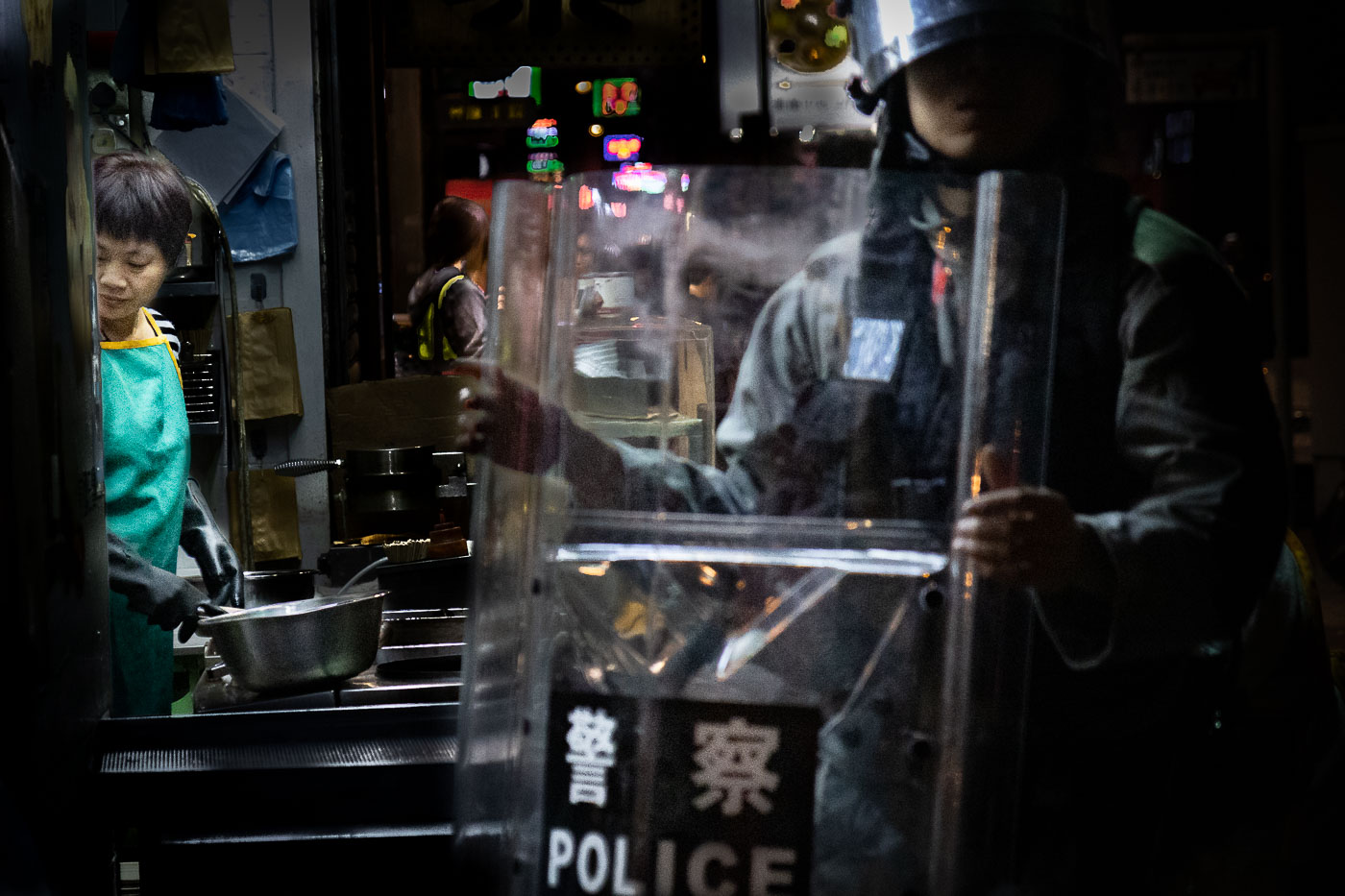 A woman continues cooking at a corner noodle shop, ignoring a riot cop standing nearby.