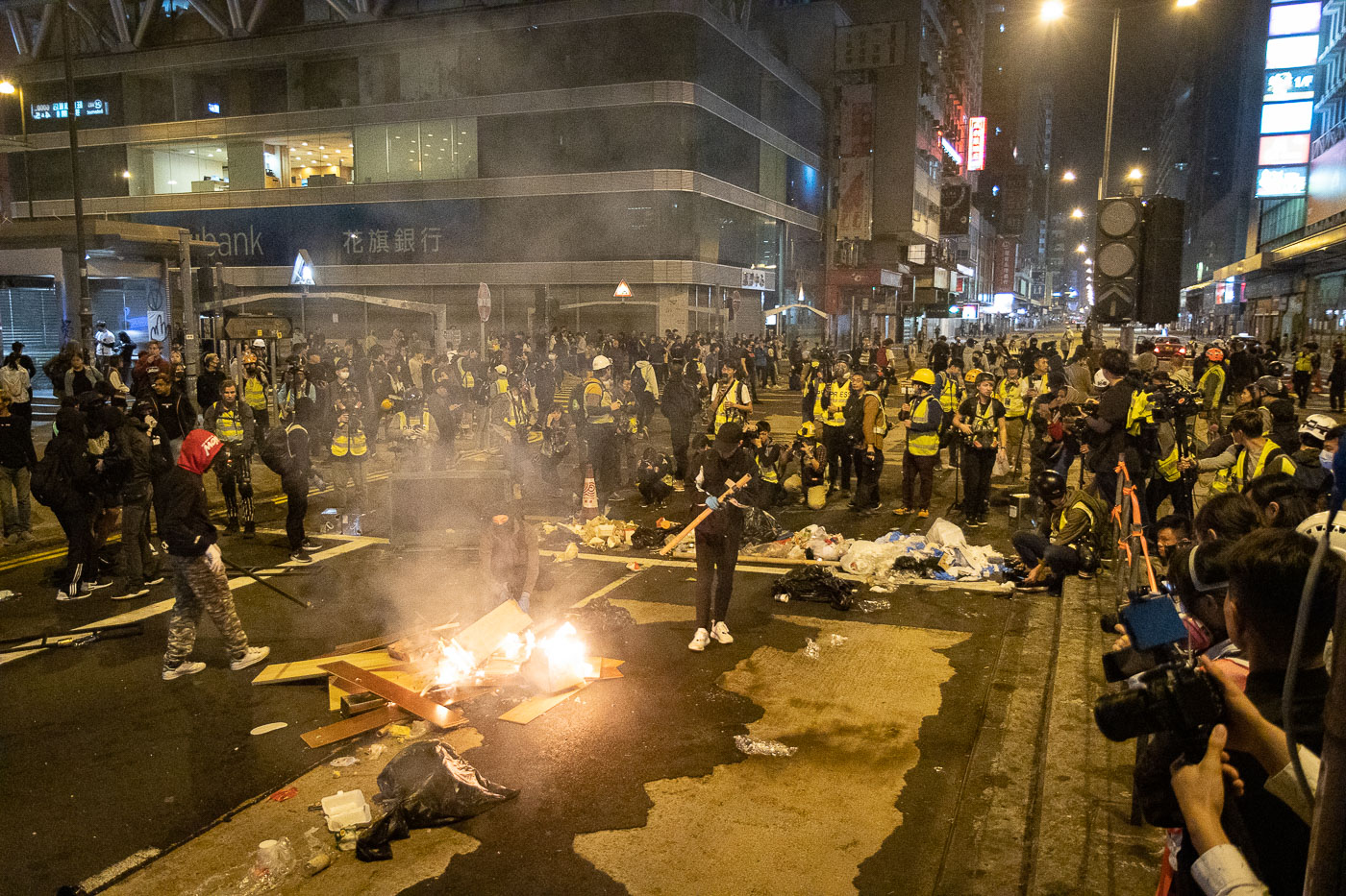 Press photographers look on as Hong Kong pro-democracy protesters set a fire in the street.