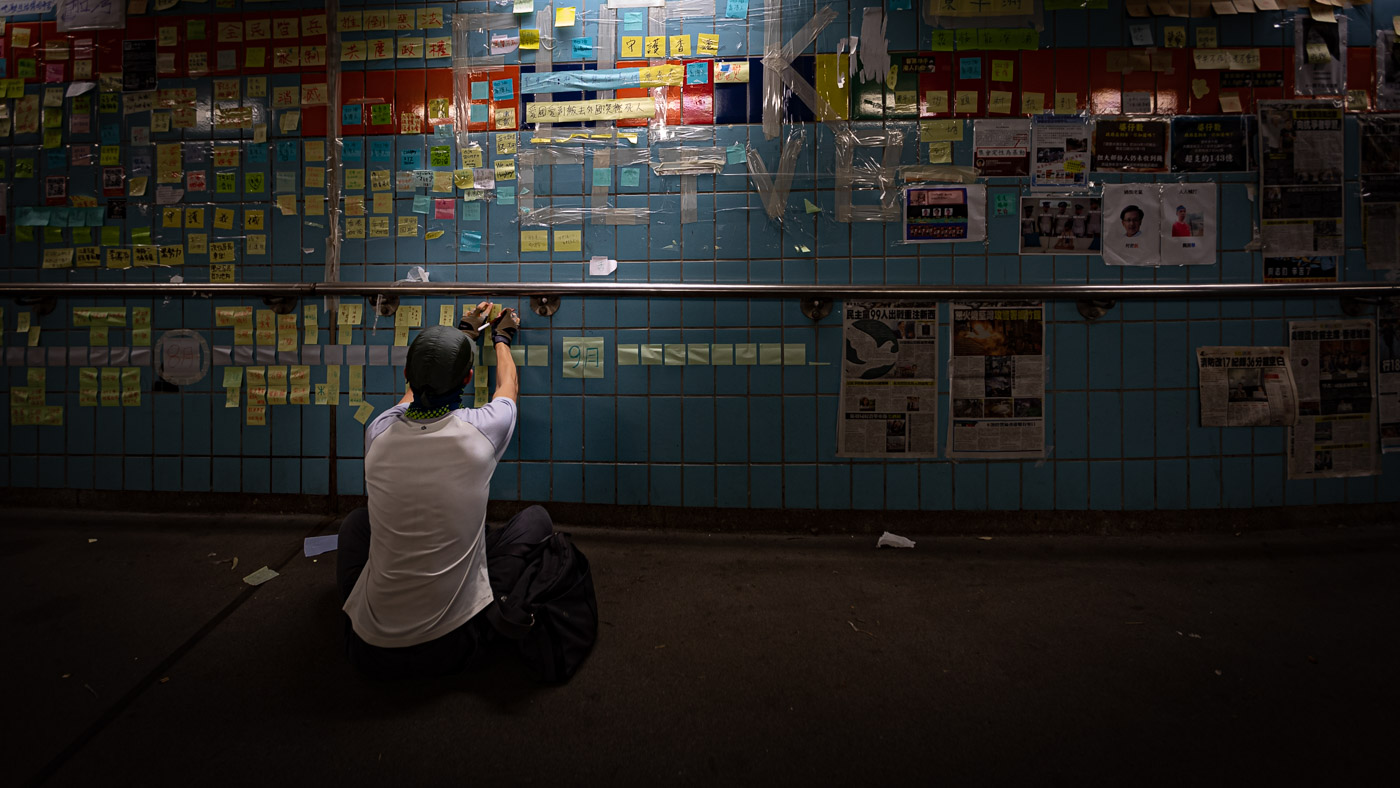Person posts a sticky note on the wall of a subway station in dim light.