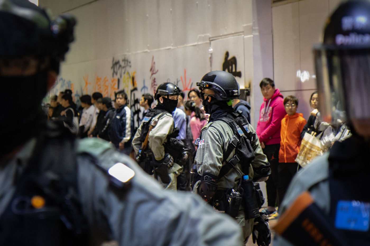 A line of civilians stand agains a wall as riot police guard them.