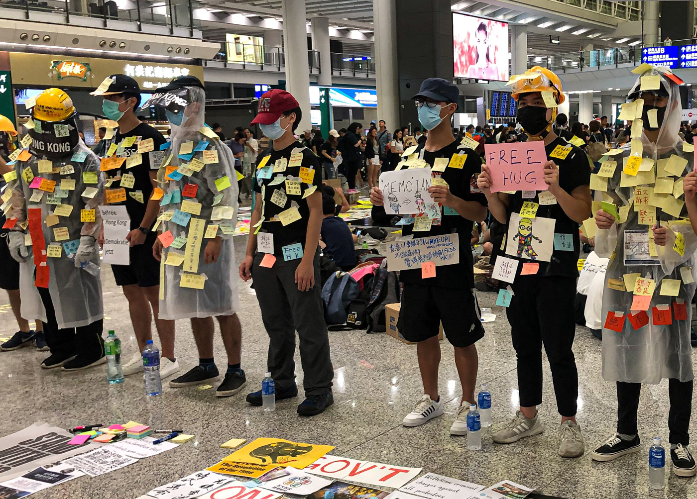 Protesters stand in the Hong Kong airport, covered in small sticky notes placed there by other protesters.