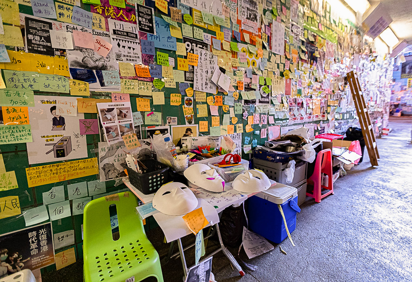 A small chair and a table full of art supplies sits against the pedestrian tunnel wall, itself covered in posters and sticky notes.
