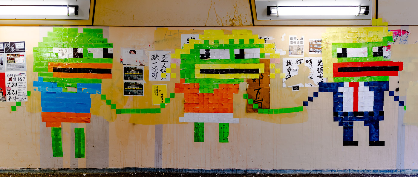 A Pepé the Frog family made from multi-colored sticky notes stuck to a wall is shown holding hands.