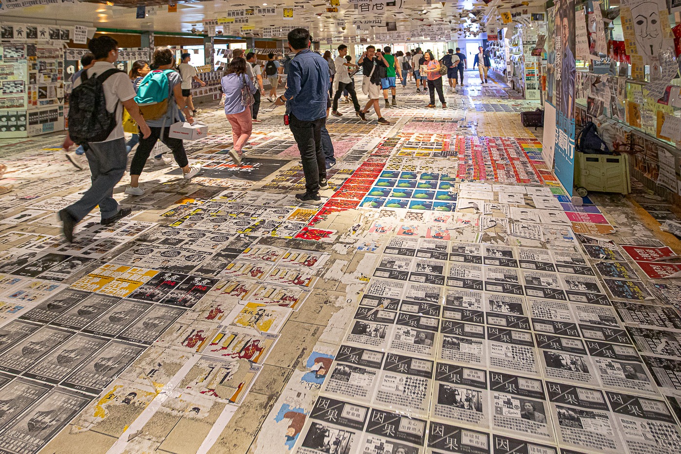 In this photo of the Tsing Yi pedestrian walkway, the floor, walls and ceiling are covered in political posters, often forcing people to walk on images of disliked political leaders.