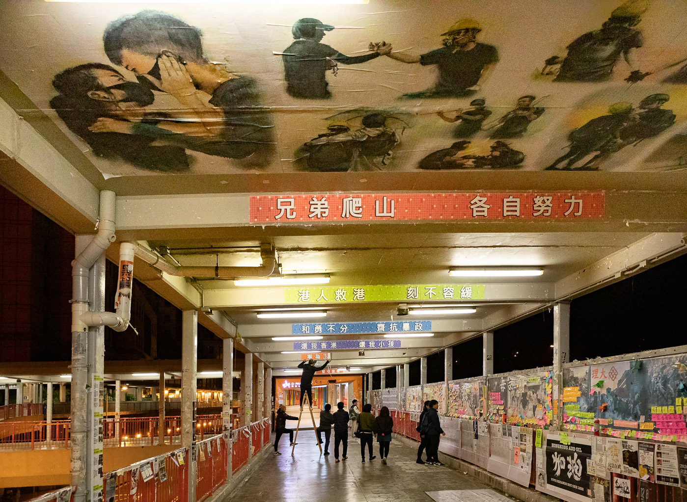 Hong Kong protesters glue posters to the ceiling of a pedestrian walkway near the Tsuen Wan MTR station.