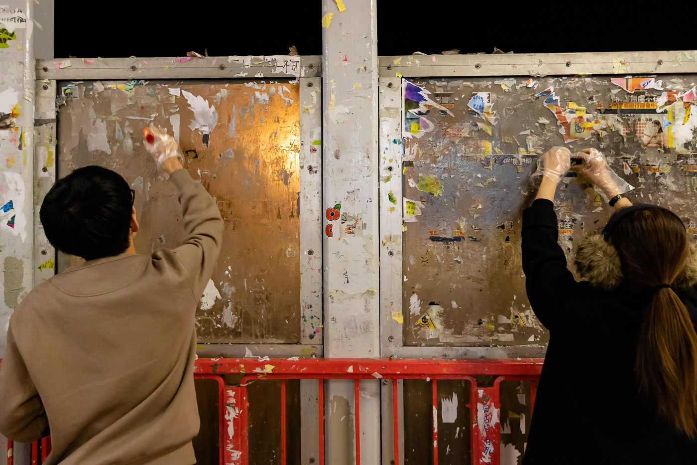 Two Hong Kong protesters clean old paper and glue off of the Tsuen Wan Lennon Wall in preparation for rebuilding it.