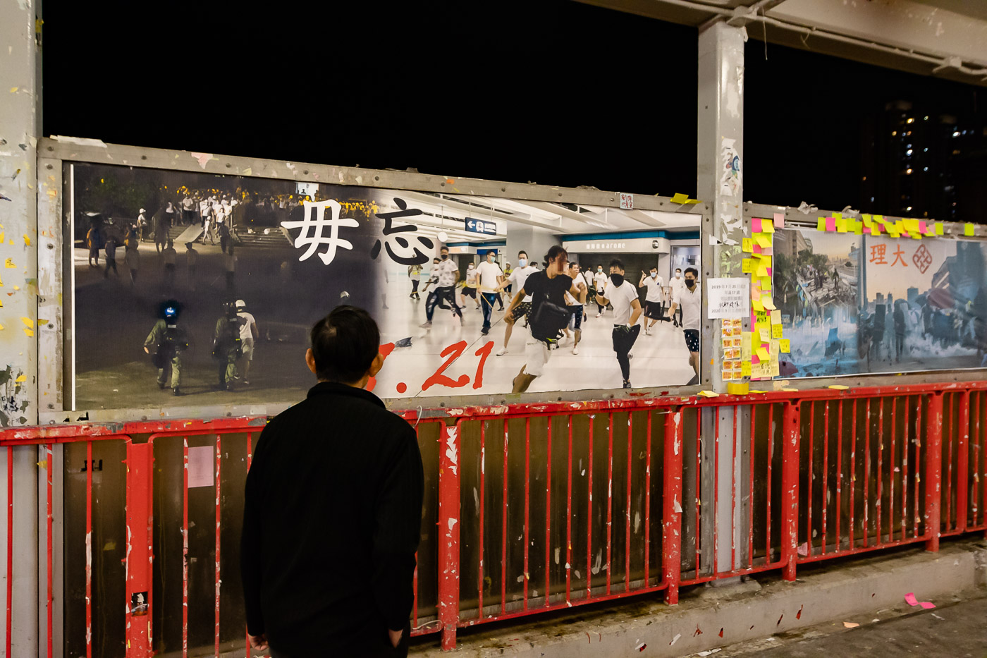A man observes posters on a Lennon Wall in Hong Kong.