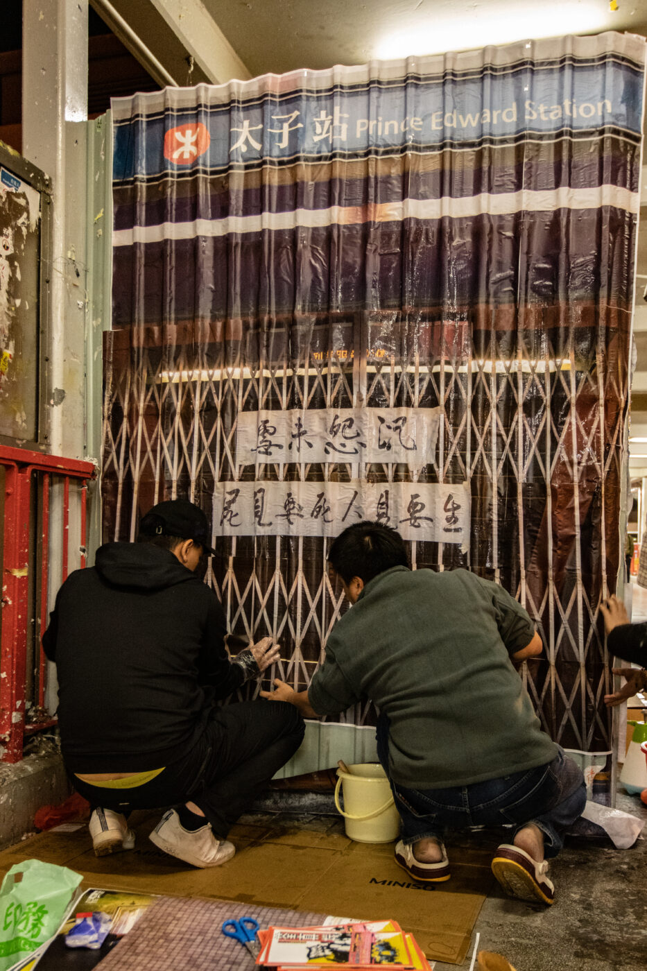 Two Hong Kong protesters glue a life-size photo of the Prince Edward MTR station to the side of a construction shed.