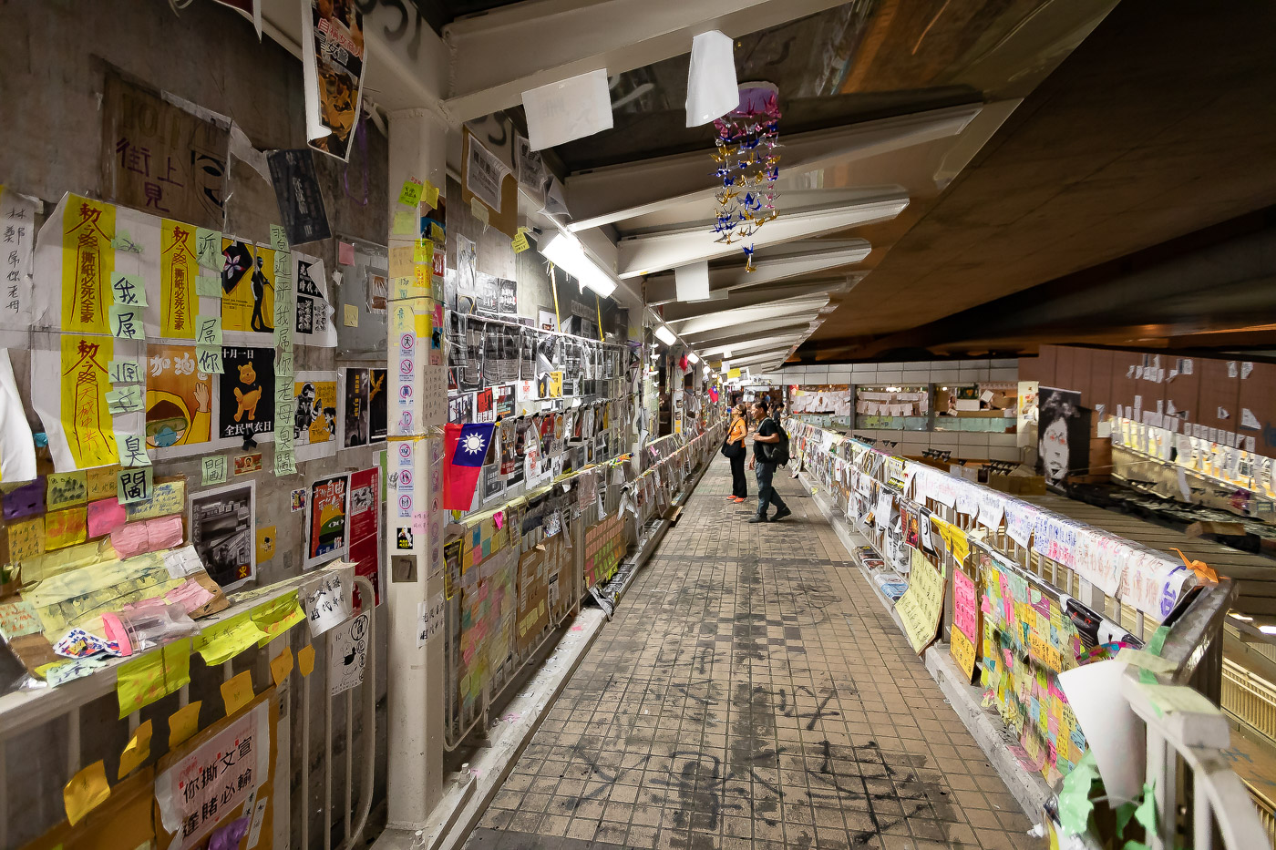 Two people stop to read posters and notes on a Lennon Wall at Tsing Yi pedestrian corridor, Hong Kong.