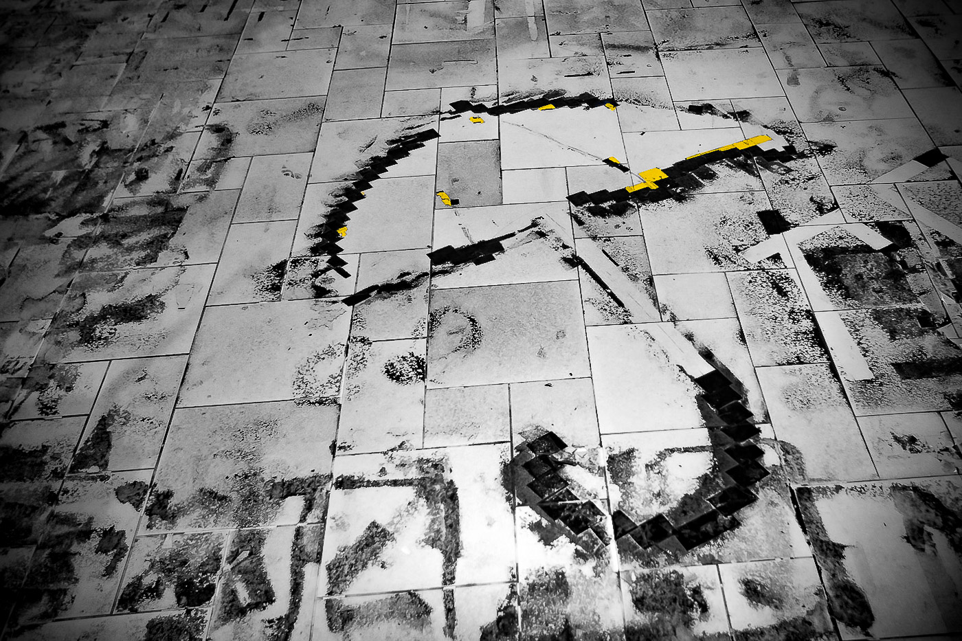 Glue and pieces of tape outline the spot on the floor where a large umbrella image had once been glued to the floor.